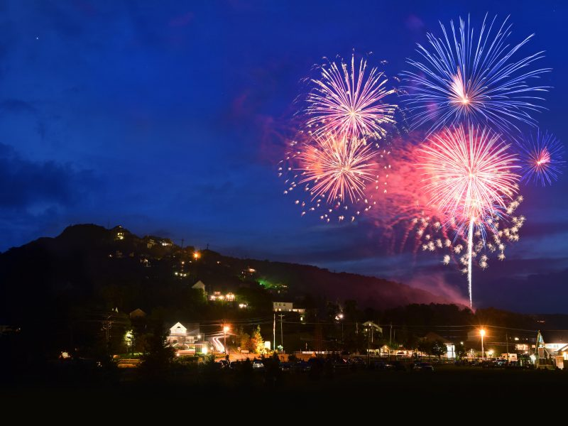 Colorful fireworks lighting up the sky over the mountain.
