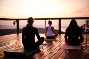 Participants practice yoga during sunrise at Beech Mountain's Summit