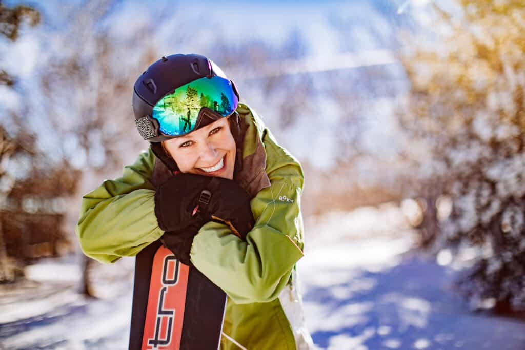 Female snowboarder in a light green jacket, black helmet and green goggles. She is smiling at the camera, holding her snowboard.