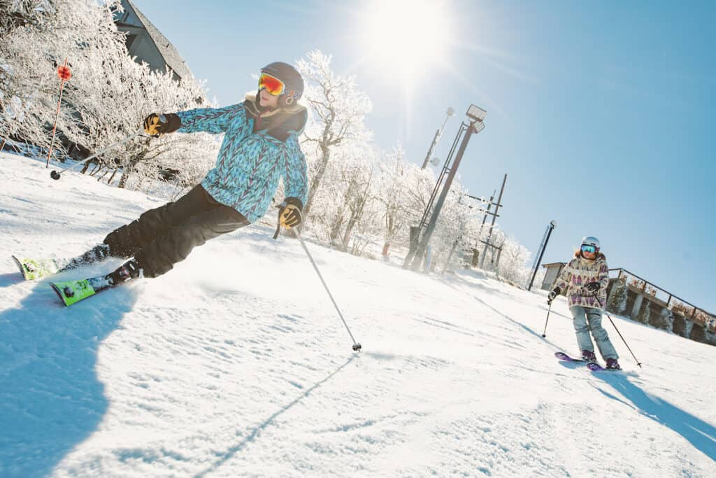 Two female skiers, skiing down Beech Mountain Resort.