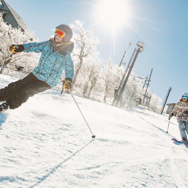 Two female skiers, skiing down Beech Mountain Resort.
