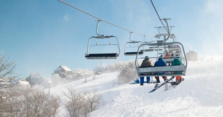 People riding the ski lift up to the top of the mountain.