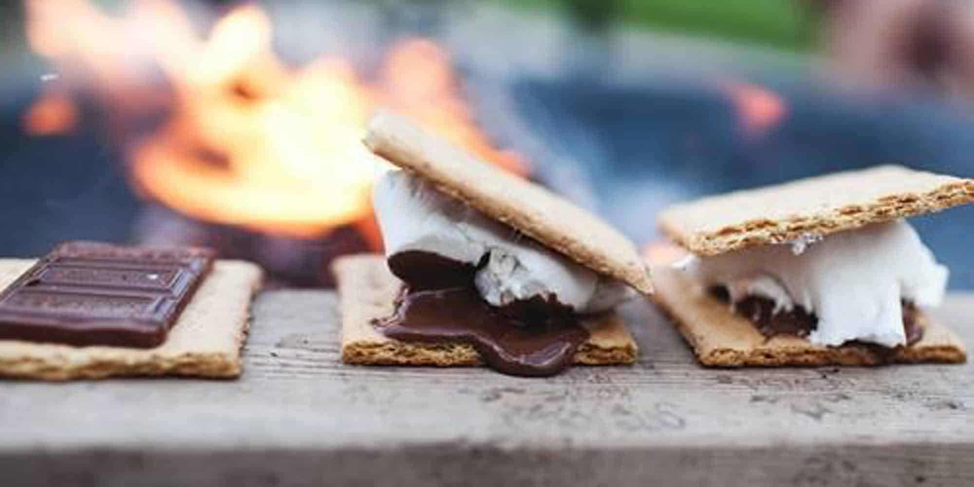 Picture of S'more sitting on a bench infront of a fire.