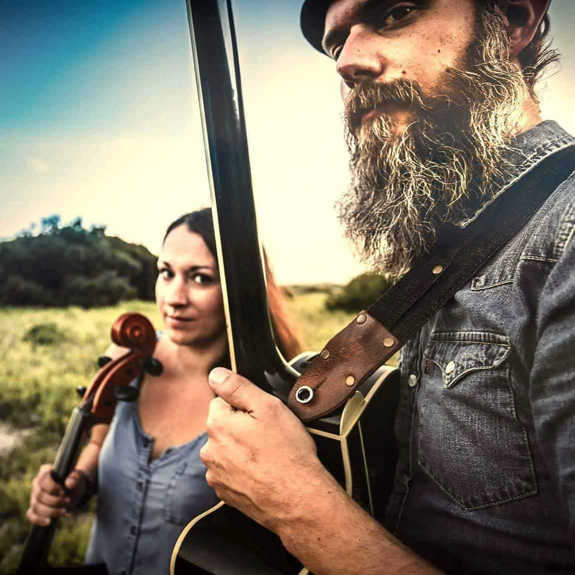 Man and woman stand next to each other holding their instruments.